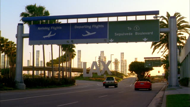 wide shot traffic entering lax airport area w/signs - lax airport stock videos & royalty-free footage