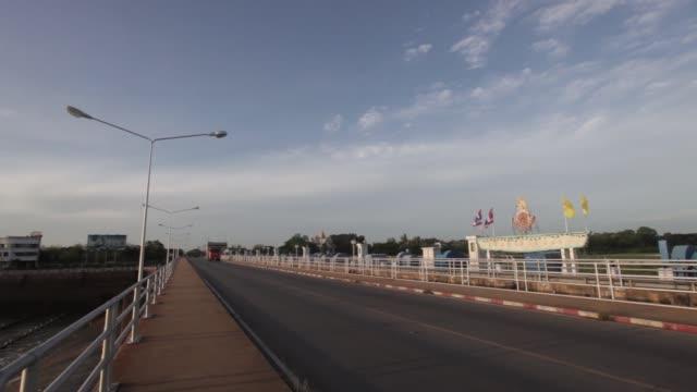 wide shot traffic moves along a road along the chao praya dam in subpaya district chainat province thailand wide shot the national flag of thailand... - チャオプラヤ川点の映像素材/bロール