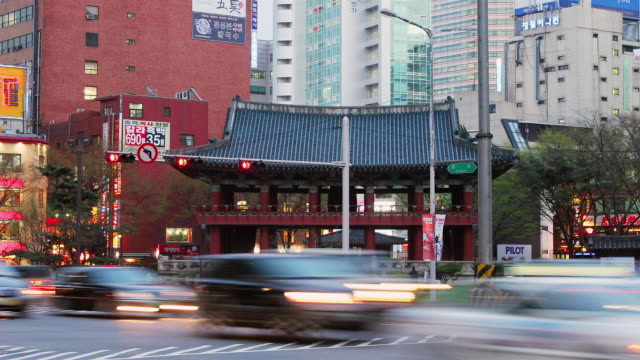 wide shot traffic moving by the bosingak pavilion in insadong as day turns to night / seoul, south korea - 韓国文化点の映像素材/bロール