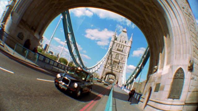 wide shot traffic moving on street and people walking on sidewalk over tower bridge / london, england - 跳開橋点の映像素材/bロール