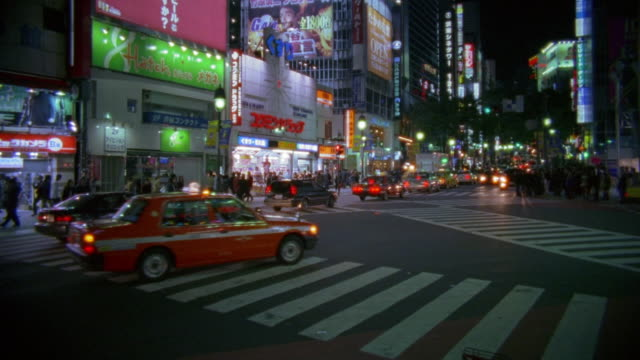 Wide shot traffic on busy street and pedestrians on sidewalk at intersection / Tokyo, Japan