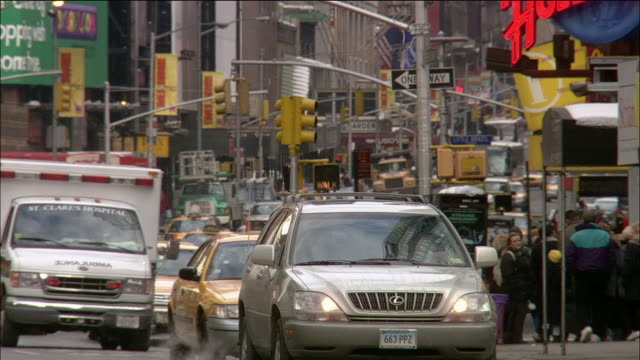 Wide shot traffic on busy street in midtown Manhattan / car stopping / New York City