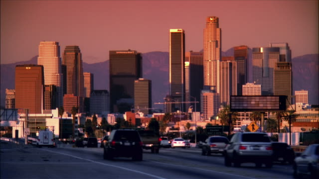 wide shot traffic on the harbor freeway with downtown skyline in background / dusk /  los angeles, california - beverly hills stock-videos und b-roll-filmmaterial