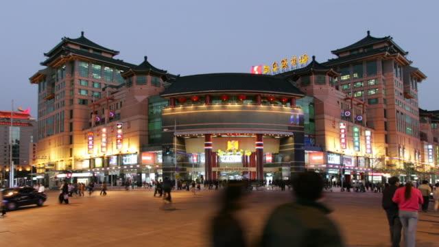 Wide shot traffic outside Sun Dong An Plaza on Wangfujing Street at twilight / Beijing