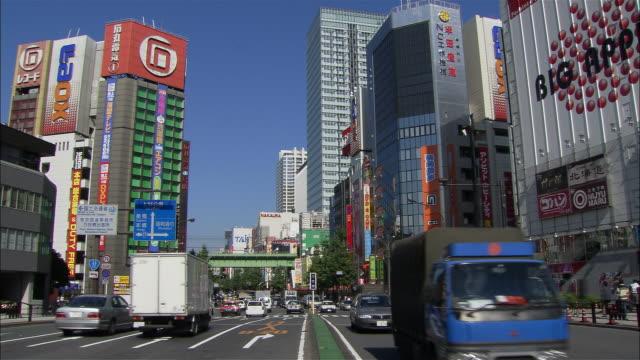 Wide shot traffic passing electronics stores on Chuo Dori in Akihabara district / Tokyo