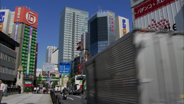wide shot traffic passing electronics stores on chuo dori in akihabara district / tokyo - ladenschild stock-videos und b-roll-filmmaterial