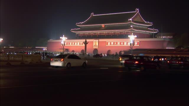 vídeos de stock, filmes e b-roll de wide shot traffic passing tiananmen square and gate of heavenly peace at night/ beijing, china - portão da paz celestial de tiananmen