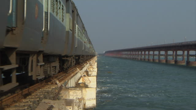 wide shot train passing by on pamban bridge - 1 minuto e più video stock e b–roll