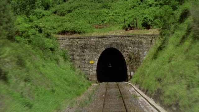 wide shot train point of view entering tunnel through hill - tunnel stock videos & royalty-free footage