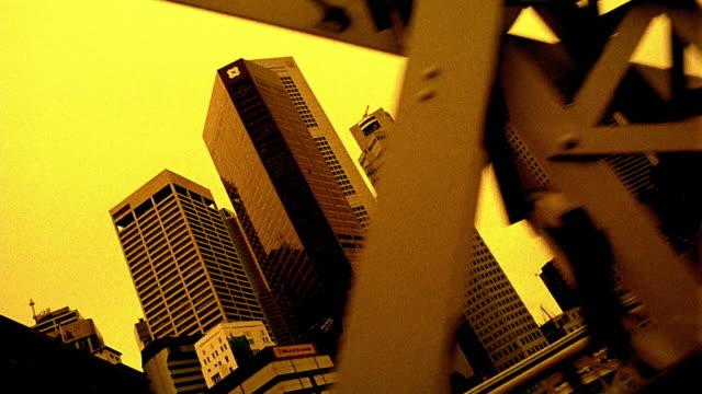 vídeos y material grabado en eventos de stock de wide shot train point of view on bridge passing skyscrapers in downtown singapore - imagen virada