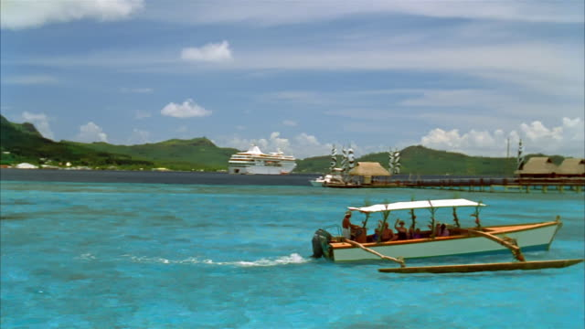 Wide shot tree-covered Mount Otemanu rising up from blue-green water / pan boat carrying passengers to island / Bora Bora