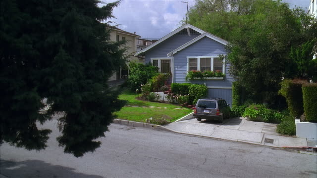 vídeos de stock, filmes e b-roll de 2005 wide shot trees growing outside blue suburban house with car in driveway/ los angeles, california, usa - entrada para carros