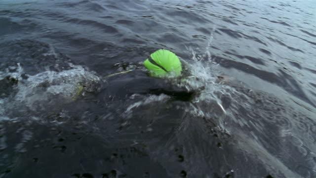 wide shot triathlete in wetsuit swimming in lake - triathlon stock videos & royalty-free footage