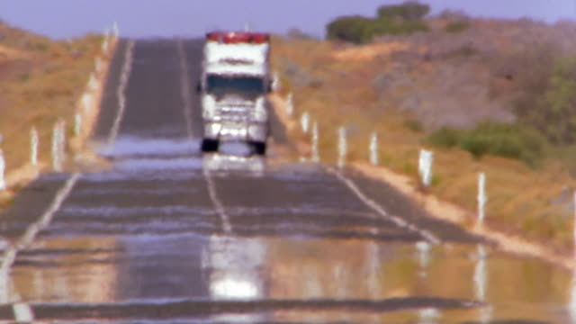 vidéos et rushes de wide shot truck driving towards cam on rural road / heatwave distortion - hot