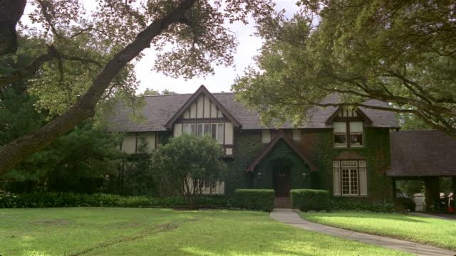 vídeos de stock, filmes e b-roll de wide shot tudor style suburban house and lawn/ san antonio, texas - facade