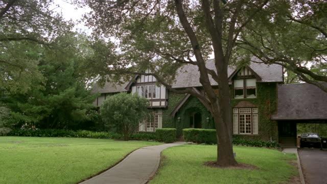 vídeos de stock e filmes b-roll de wide shot tudor style suburban house and lawn/ san antonio, texas - tudor