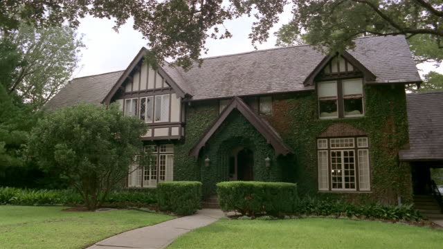 Wide shot Tudor style suburban house and lawn/ San Antonio, Texas