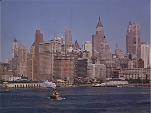 1939 Wide shot Tugboat traveling on Hudson River near skyscrapers and Lower Manhattan waterfront / Manhattan, New York City, New York, USA