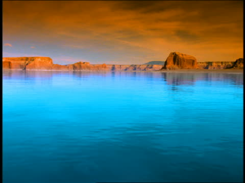 wide shot turquoise water with desert buttes in background / lake powell, utah / filter - ユタ州点の映像素材/bロール