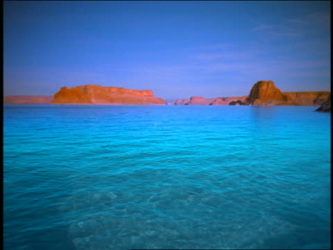 wide shot turquoise water with desert buttes in background / splash in lake / lake powell, utah - lake powell stock videos & royalty-free footage