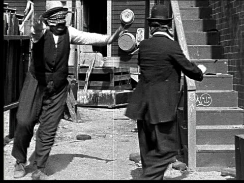 1918 b/w wide shot two blindfolded men finding each other in alley, embracing, and dancing - menschliche gliedmaßen stock-videos und b-roll-filmmaterial
