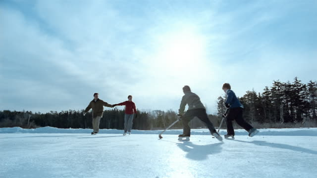 wide shot two boys playing hockey on frozen pond / couple skating and holding hands / maine - grandangolo tecnica fotografica video stock e b–roll