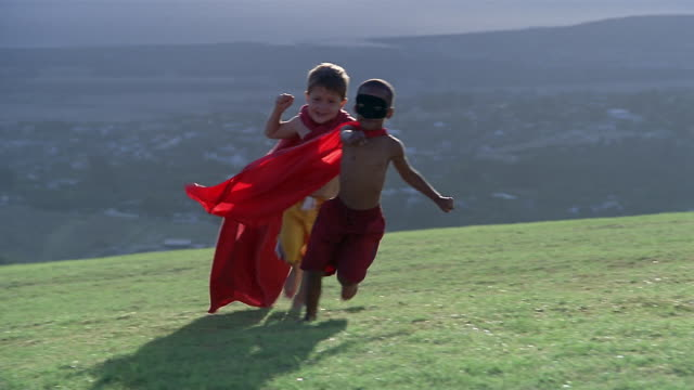 Wide shot two boys wearing swimming trunks and capes running around sprinkler on lawn / South Africa