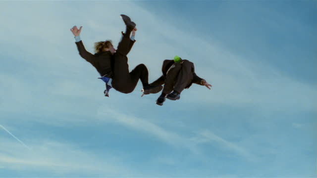 Wide shot two business men in midair after jumping on trampoline / one kicking other in midair / both men bounce up again