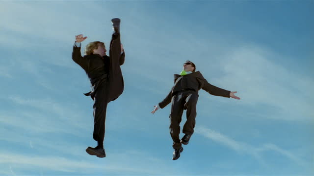 vidéos et rushes de wide shot two business men in midair after jumping on trampoline, with one nearly kicking other's head in midair - souplesse