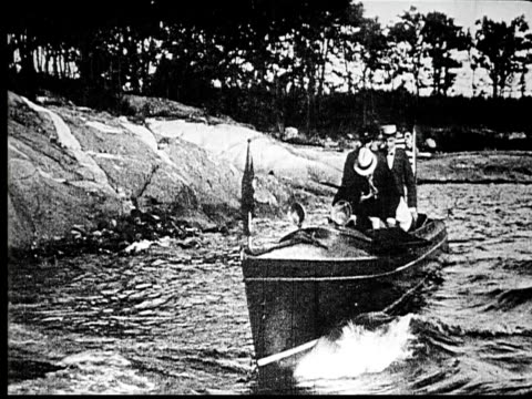 1914 b/w wide shot two businessmen arriving on island in small boat and jumping onto shore  - 1914 stock videos & royalty-free footage
