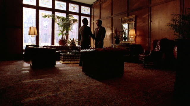 wide shot pan two businessmen shaking hands in lobby of brown palace hotel / they exit / denver, co - 1993 stock videos & royalty-free footage