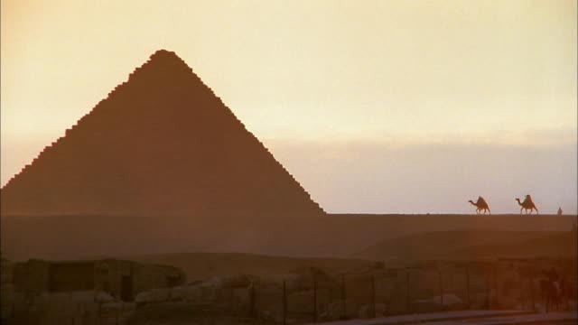 wide shot two camels approaching pyramid at giza / egypt - pyramid bildbanksvideor och videomaterial från bakom kulisserna