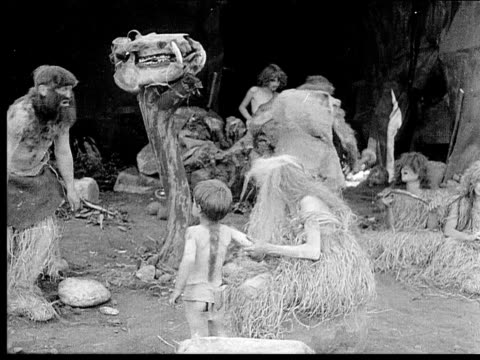 1914 B/W Wide shot Two caveman leaving cave with weapons