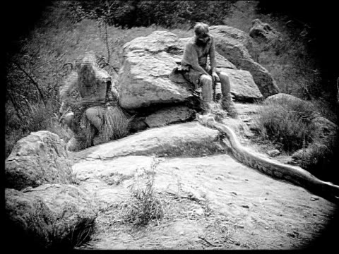 1914 B/W Wide shot Two caveman sitting on rocks near snake and running away