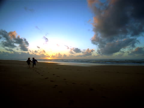 wide shot two children holding hands and running on the beach towards the ocean / morocco - anno 2001 video stock e b–roll