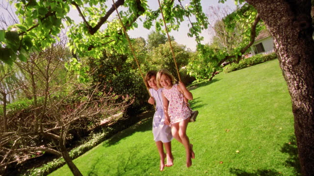 CANTED wide shot two girls swinging on tree swing toward camera smiling + sticking out tongues