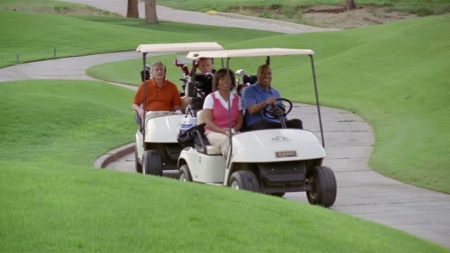 wide shot two golf carts riding down path/ pan carts stopping and three men and woman getting out, selecting clubs and walking onto green/ phoenix, arizona - golf cart stock videos and b-roll footage