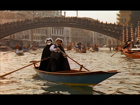Wide shot two gondoliers in period costume steering gondola along canal / Venice, Italy