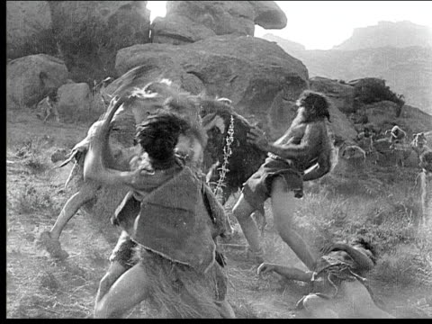 1914 b/w wide shot two groups of cavemen fighting with weapons during battle - fight stock videos & royalty-free footage