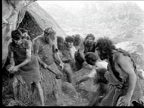 1914 B/W Wide shot Two groups of cavemen fighting with weapons outside cave entrance