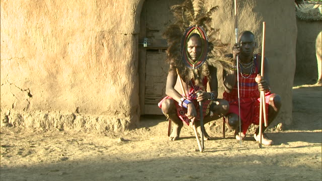 Wide Shot - Two Masai men squat outside a hut with their weapons in Africa / Kenya