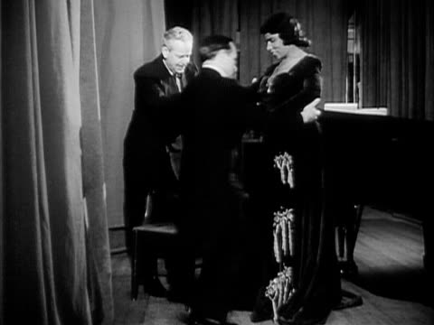 vídeos de stock e filmes b-roll de wide shot two men assisting contralto singer marian anderson and pouring her a glass of water after her performance at the town hall/ manhattan new... - sentar se
