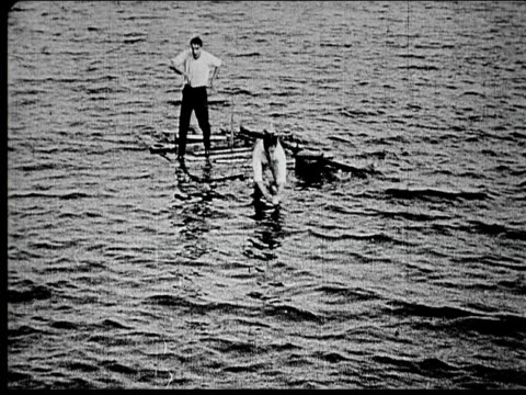 1914 B/W Wide shot Two men jumping into sea and swimming away from wooden raft