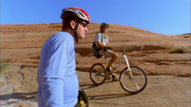 wide shot two men standing with mountain bikes in desert terrain / cyclist in foreground smiling at cam - resting stock videos & royalty-free footage
