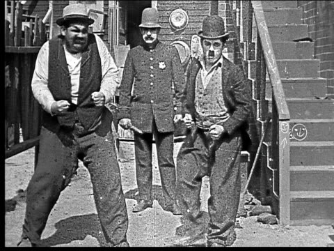 1918 b/w wide shot two men starting to fight in alley/ policeman enters and men act like they're dancing - silent film stock videos & royalty-free footage