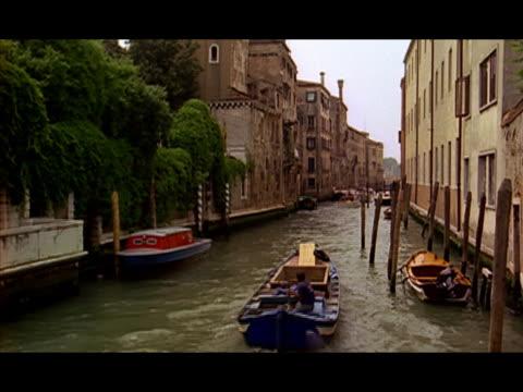 vídeos de stock e filmes b-roll de wide shot two mototboats travelling along narrow canal / venice, italy - formato letterbox