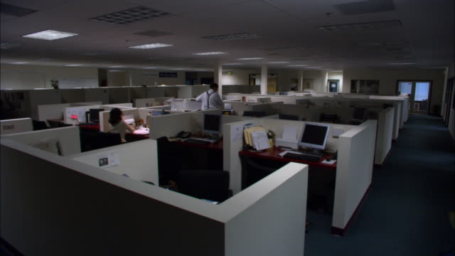 Wide shot two office workers working late in cubicles on dim office floor / one office worker leaving / low angle