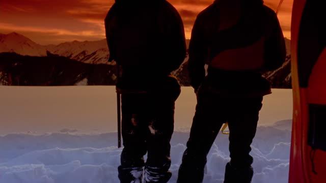 vídeos y material grabado en eventos de stock de wide shot two people standing together holding paddles next to kayak, watching sunset behind mountains background - imagen virada