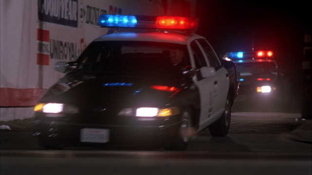 wide shot two police cars with sirens on driving out of alley at night - パトカー点の映像素材/bロール