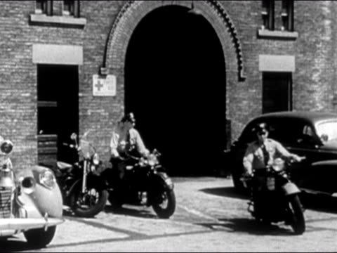 wide shot two policemen leaving station on motorcycles/ dearborn, michigan - dearborn michigan stock videos and b-roll footage